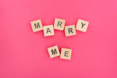 top view of marry me lettering made of wooden blocks on pink background