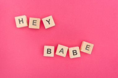 top view of hey babe lettering made of wooden blocks on pink background