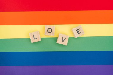 top view of love lettering made of  wooden cubes on paper rainbow background