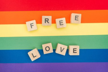 top view of free love lettering made of  wooden cubes on paper rainbow background