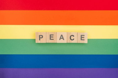 top view of pease lettering peace made of wooden cubes on paper rainbow background