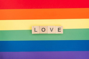top view of love lettering made of wooden blocks on paper rainbow background