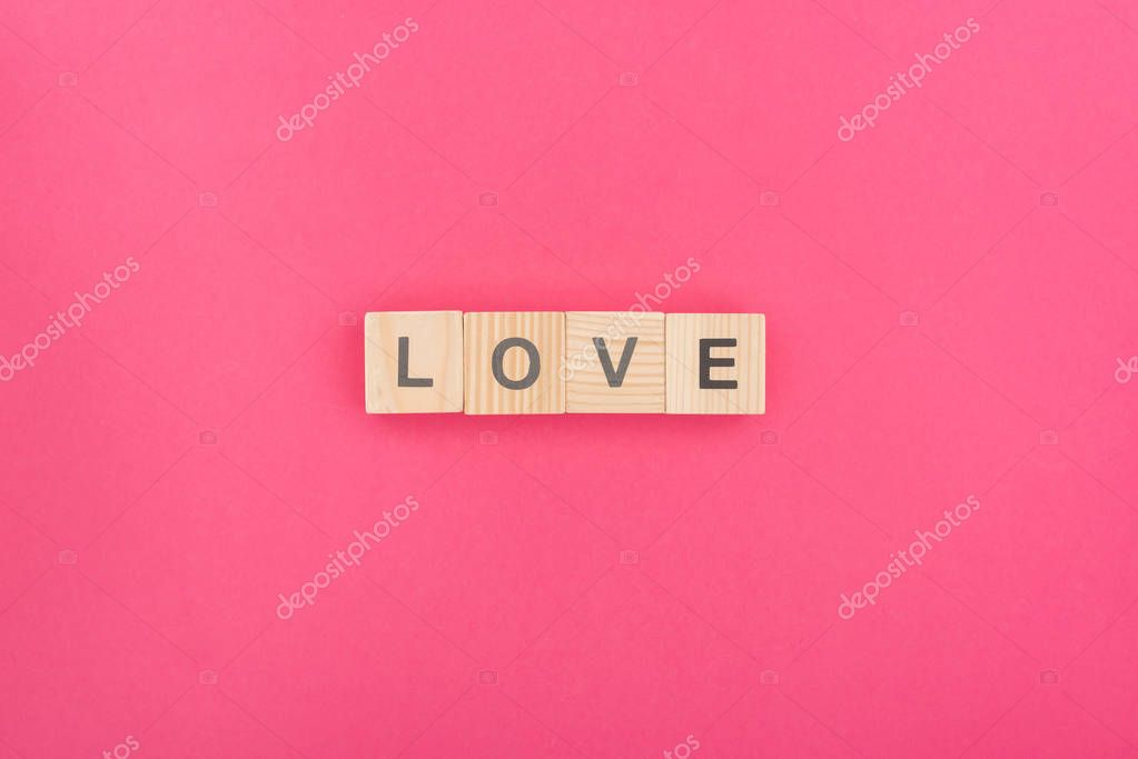 Top view of love lettering made of wooden blocks on pink background stock vector