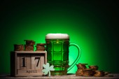 Fotografie glass of green irish beer near golden coins and cube calendar on green background
