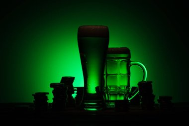 silhouette of glasses of irish beer standing on table near coins on green background
