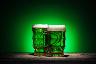 glasses of irish beer standing on wooden table on green background