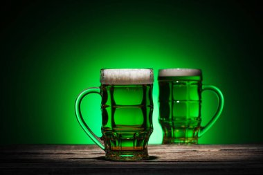 glasses of lager standing on wooden table on green background