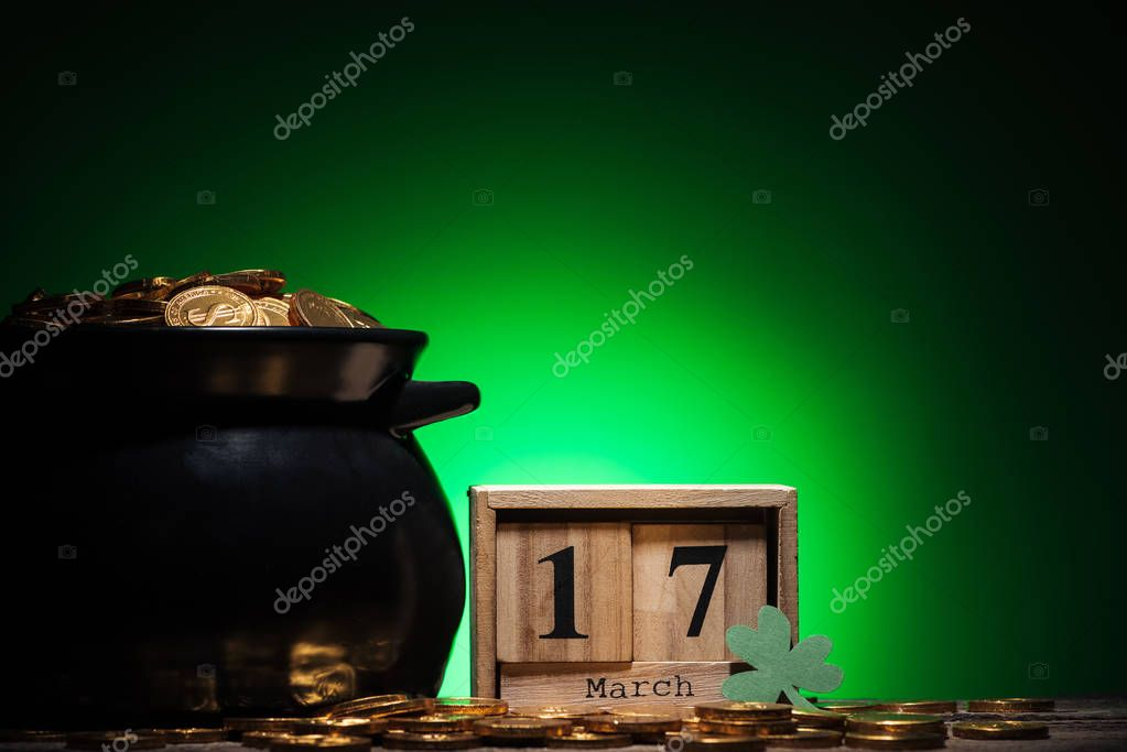 cube calendar with date near golden coins in pot on green background