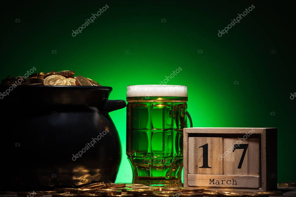 glass of irish beer near golden coins in pot and cube calendar on green background