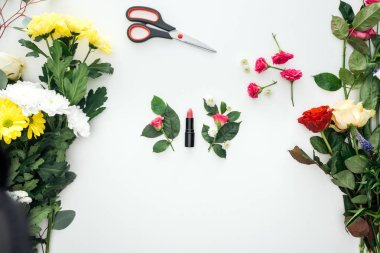Top view of pink rose buds, lipstick and scissors surrounded by flowers on white background stock vector