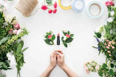 Cropped view of female hands, boutonnieres and lipstick surrounded by flowers on white background stock vector