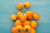 top view of orange ripe persimmons on blue background