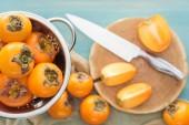 Selektivní fokus oranžové tomel v cedníku a plátky na prkénku s nožem