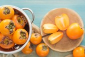Fotografie selective focus of ripe orange persimmons in colander and slices on cutting board