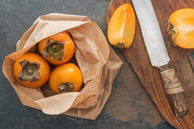 top kağıt paketindeki tüm persimmons görünümünü ve kesme tahtası üzerinde dilimlenmiş