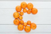 top view of letter C made of fresh tangerines on wooden white surface
