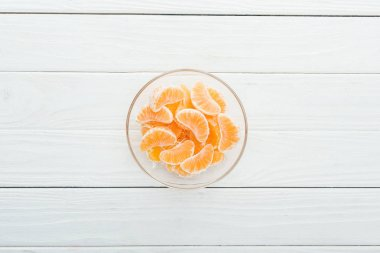 Top view of peeled tangerine slices in glass bowl on wooden white background stock vector