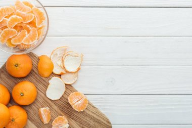 Top view of peeled tangerines on wooden cutting board on white wooden table stock vector