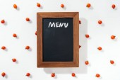 Fotografie top view of chalk board with menu lettering among cherry tomatoes
