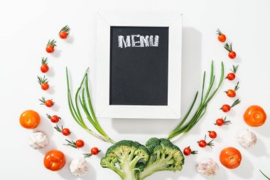 Chalk board with menu lettering among tomatoes, broccoli, onion and garlic stock vector