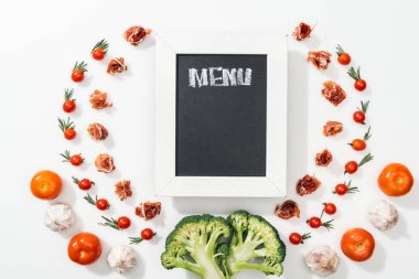 Chalk board with menu lettering among tomatoes, prosciutto, broccoli, onion and garlic stock vector
