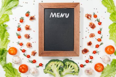 Top view of chalk board with menu lettering among tomatoes, lettuce leaves, prosciutto, broccoli, spices and garlic stock vector