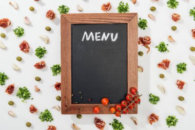 Chalk board with menu lettering among prosciutto, olives, garlic cloves, greenery and cherry tomatoes stock vector