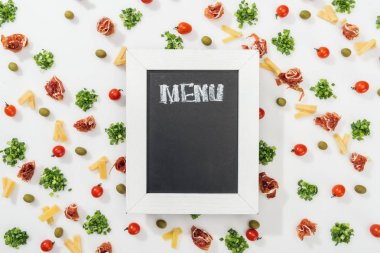 Chalk board with menu lettering among olives, prosciutto, greenery, cut cheese and cherry tomatoes stock vector