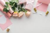 Fotografia vista superiore di rose rosa, rotoli di cartacei, avvolti regali e busta su priorità bassa grigia