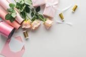 Fotografia vista superiore di Rose, rotoli di carta, regali spostati, busta, biglietto di auguri e rocchetti di filo su sfondo grigio