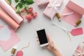 oříznutý pohled ženy držící smartphone v blízkosti růží, role papíru, zabalené dárky, obálky, blahopřání a špulky nití na šedém pozadí