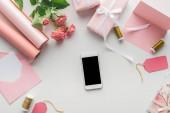 pohled shora smartphone u růže, role papíru, zabalené dárky, obálka a špulky nití na šedém pozadí