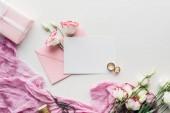 pohled shora na prázdnou kartu s růžovou obálku, květiny, hadřík, zabalený dárek, nůžky a zlaté snubní prsteny na bílém pozadí