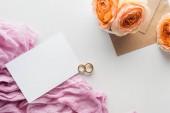 pohled shora prázdné karty, obálky, květin, hadřík a zlaté snubní prsteny na šedém pozadí
