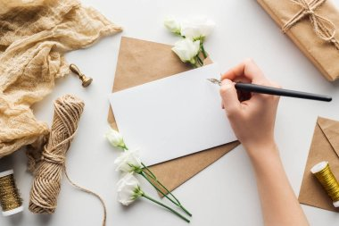 cropped view of woman writing in card with ink pen near eustoma, cloth, envelope and wrapped gift on grey background