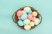 Fotografie top view of pastel easter eggs in wicker basket isolated on blue