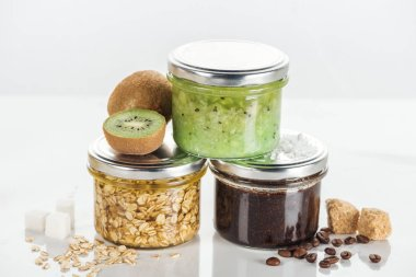 glass jars with homemade cosmetics, kiwi and brown sugar cubes on white surface