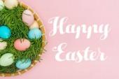 Fotografie Draufsicht der bemalten Eiern in Wicker-Platte mit Grass isoliert auf rosa mit Schriftzug Frohe Ostern