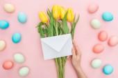 Teilansicht der Frau, die Hülle isoliert auf rosa Tulpe Blumen und Ostereier