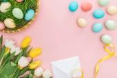 Draufsicht der Ostereier in Wicker Platte, Tulpen und Umschlag isoliert auf rosa