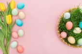 top view of tulip flowers and pastel easter eggs in wicker plate isolated on pink