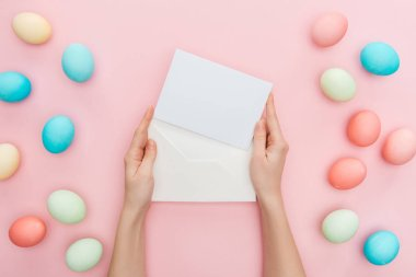cropped view of female hands with greeting card and envelope isolated on pink with pastel easter eggs