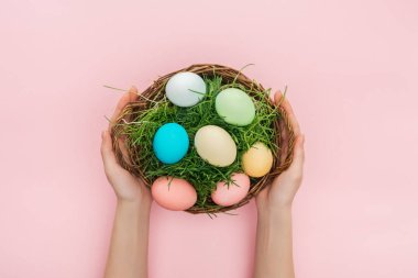 Cropped view of female hands holding wicker plate with grass and easter eggs isolated on pink stock vector