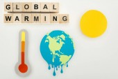 řezání papíru tání země a slunce, teploměr s označením vysokou teplotou v měřítku a dřevěné kostky s globálního oteplování nápisy na šedém pozadí