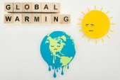 Papierschnitt schmelzende Erde und Sonne mit traurigem Gesichtsausdruck, Thermometer mit hoher Temperatur auf Skala und Schriftzug globale Erwärmung auf Holzwürfeln auf grauem Hintergrund