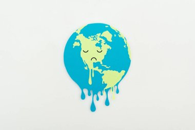 melting paper cut globe with sad face expression on grey background, global warming concept