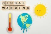 papír vágások olvadó föld és a nap-Szomorú arc-kifejezések, hőmérővel és fából készült kocka, a globális felmelegedés felirat szürke háttér