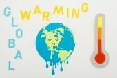 Papiergeschnittene Schmelzkugel mit traurigem Gesichtsausdruck, Schriftzug globale Erwärmung und Thermometer mit Hochtemperaturanzeige auf Skala auf grauem Hintergrund