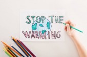 partial view of woman writing stop the warming on card with earth sign, and multicolored pencils on white background