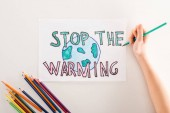 partial view of woman writing stop the warming on card with globe sign, and multicolored pencils on white background